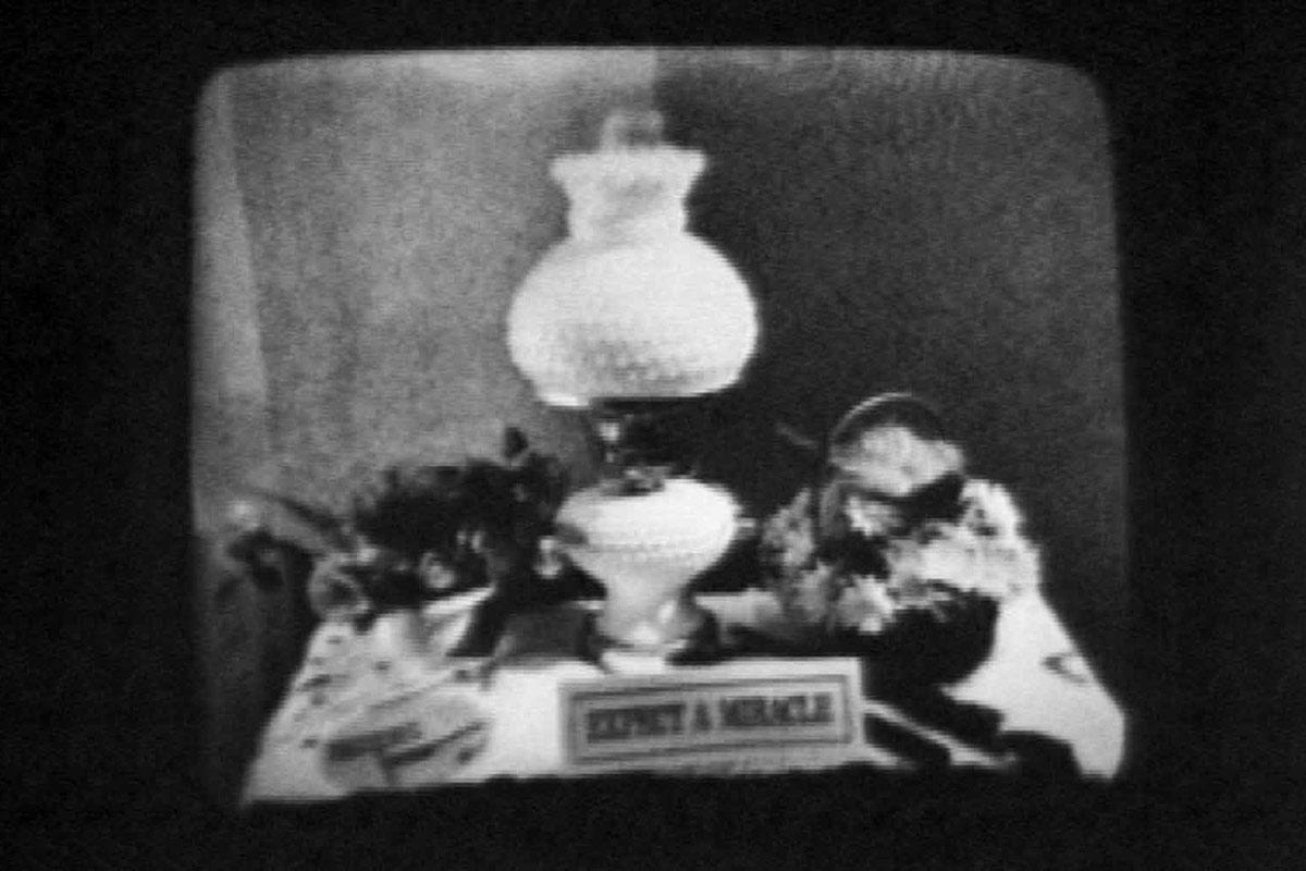 "black and white image of a lamp on a table and a small sign that says ""Expect a Miracle"""