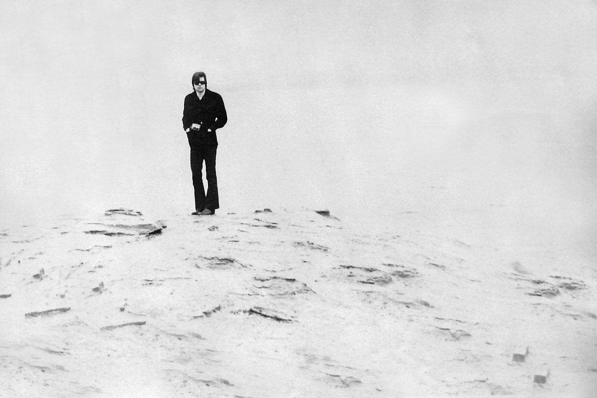 black and white image of man standing on shoreline wearing all black.  The foreground and background are very light.