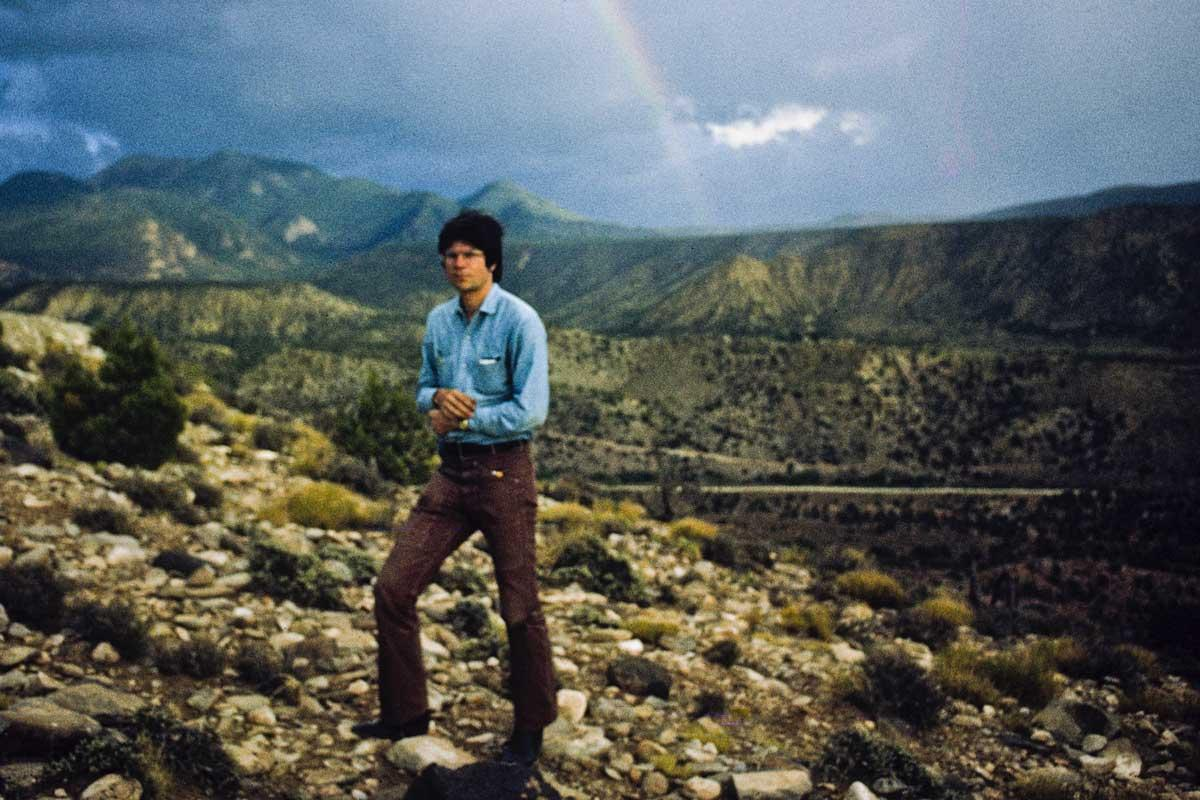 a man standing on. rocky ground with mountains and a rainbow in the background