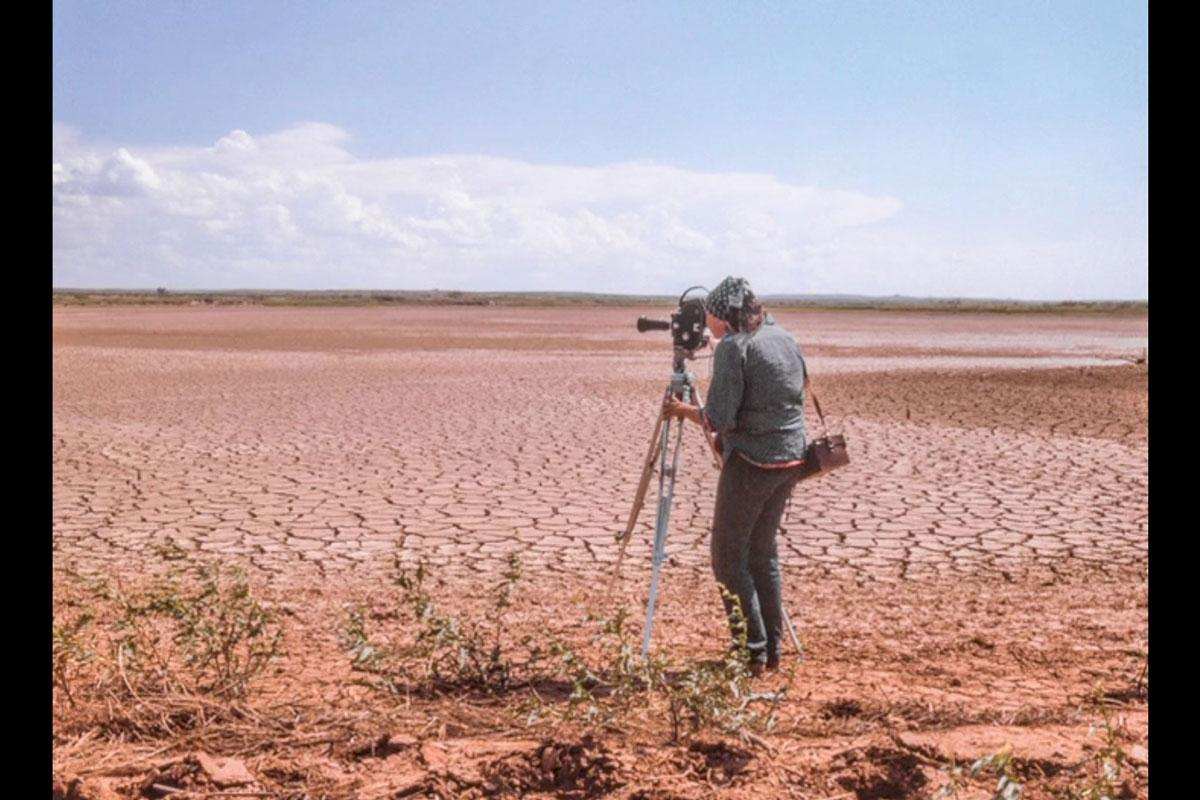A person looking through a film camera on a tripod, overlooking a dry lakebed.