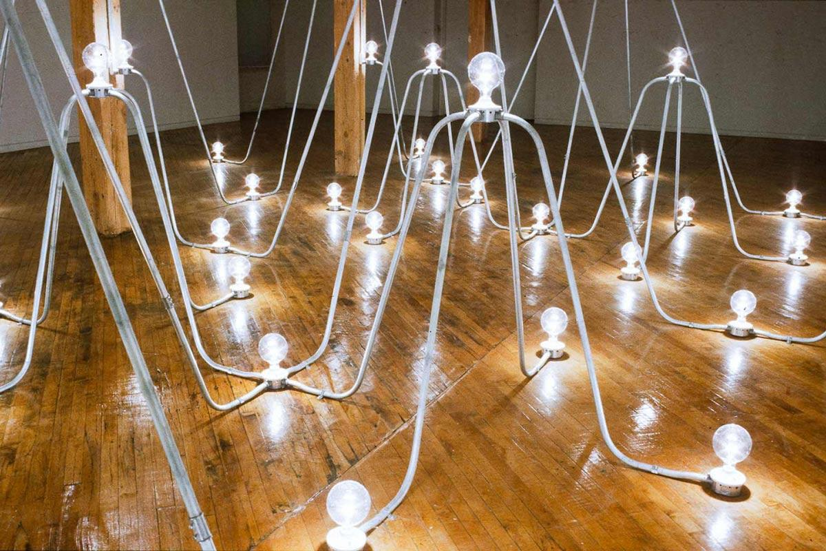 a sculpture made of arches of conduit with lightbulbs on the floor and at the peaks of the arches