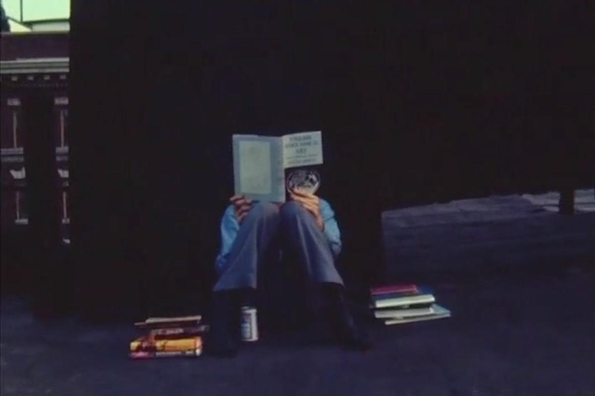 a person sitting on the ground reading with their back against a dark wall and a pile of books sitting on either side of them