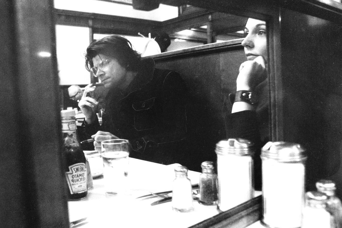 two people site at a diner table looking forward, one smokes a cigarette. black and white.