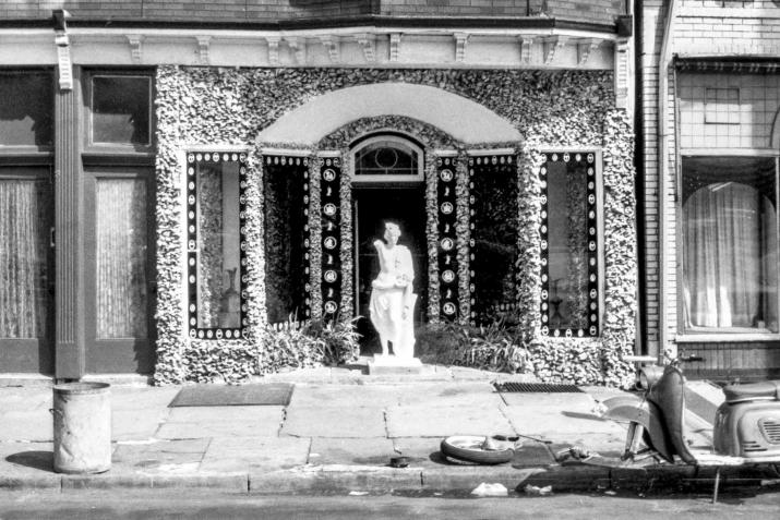 A white figurative statue in front of a heavily textured storefront in Passaic, New Jersey