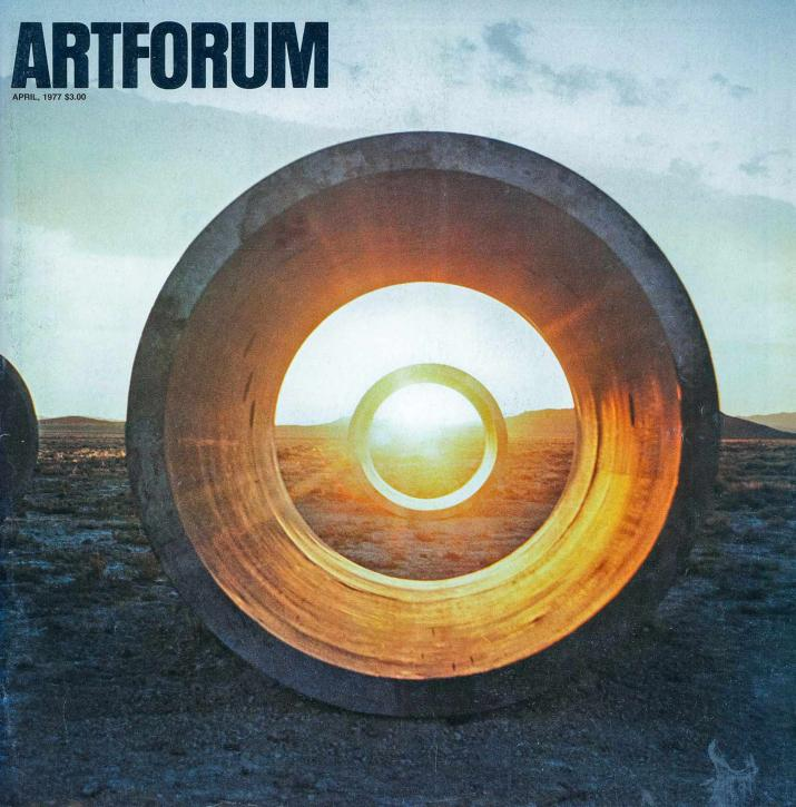 Cover of Artforum magazine with black logo in top left and image of circular concrete tunnels with sun setting in background.