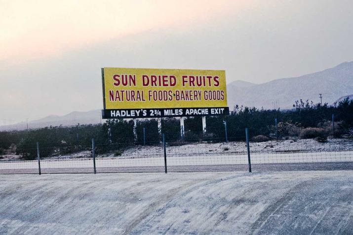 "a sign that says ""Sun Dried Fruits"" above a concrete culvert"