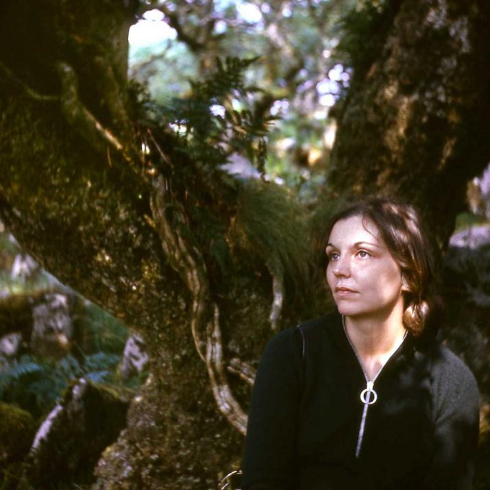 A woman leaning against a mossy tree with dappled light