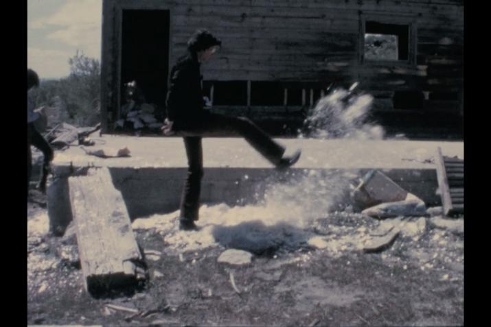 a man kicking a pile of mica and the mica is flying up in the air in front of a small wood cabin