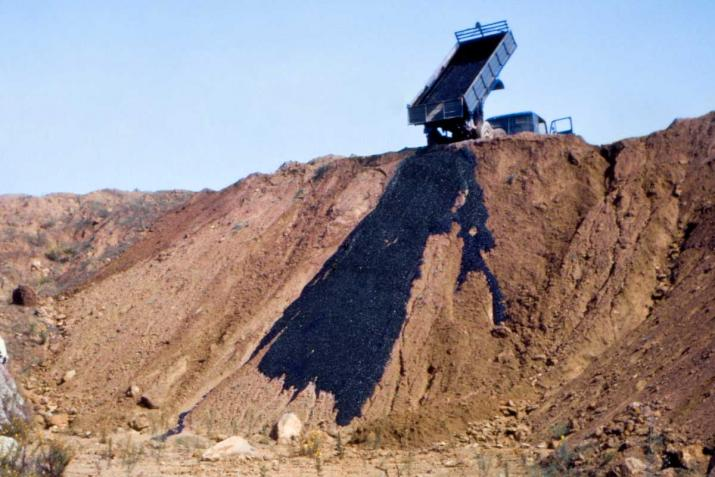 a truck dumping black asphalt onto an earthen hillside