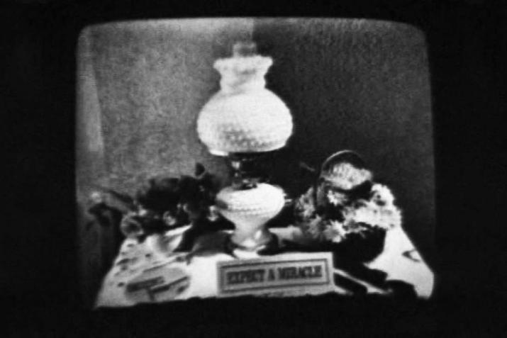 "a black and white image of a lamp on a messy desk and a small sign that reads ""expect a miracle"""