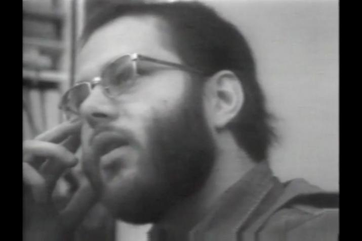 Black and white image of a man with a beard and glasses talking looking to the left.