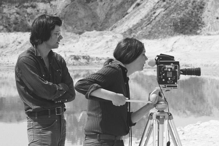 black and white image of two figures. One stands behind and one looks through the viewfinder of a Bolex film camera on a tripod