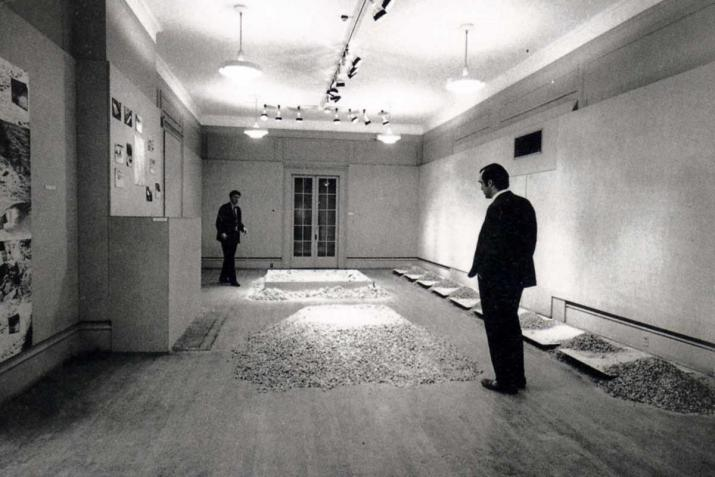 small room with two figures looking at sculptures made of salt and mirrors on the floor, black and white.
