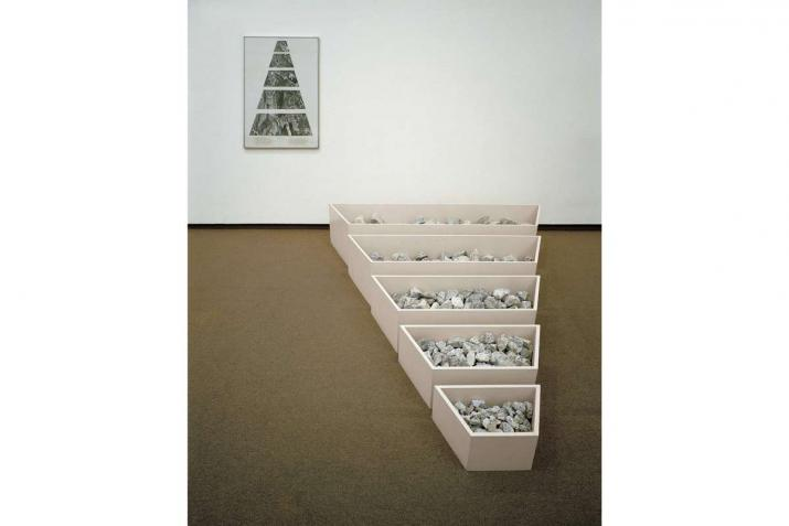 Five low bins full of rocks arranged on the floor from largest to smallest. On the wall is a framed collage of a map that shows the same shapes.