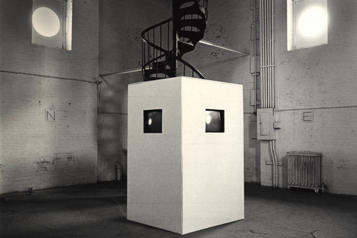 a white box with two screens in embedded inside sits in the center of a white brick room with a spiral staircase at the back and two high windows.