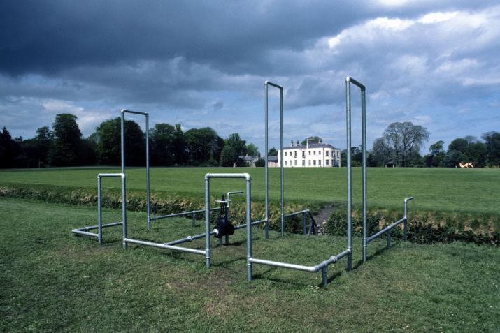 a structure built of galvanized steel pipes built in a grassy field