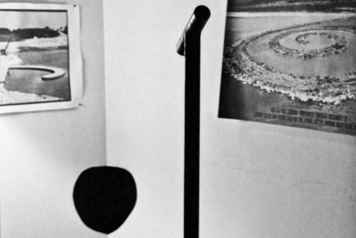 a vertical steel pole with a horizontal viewing pipe directed at a black circle painted in the corner of a room