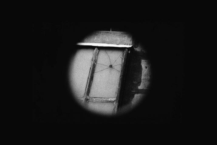 black background with a black and white circle in the center that displays a cracked window.
