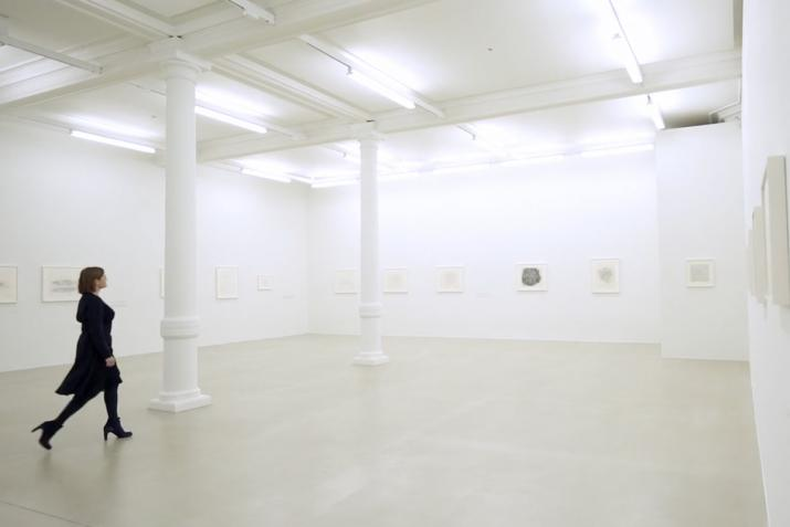 figure walking through an art gallery with white walls