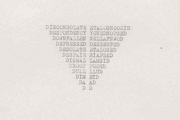 a yellowing piece of letter size paper with words typewritten in the shape of an inverted triangle in the center of the paper