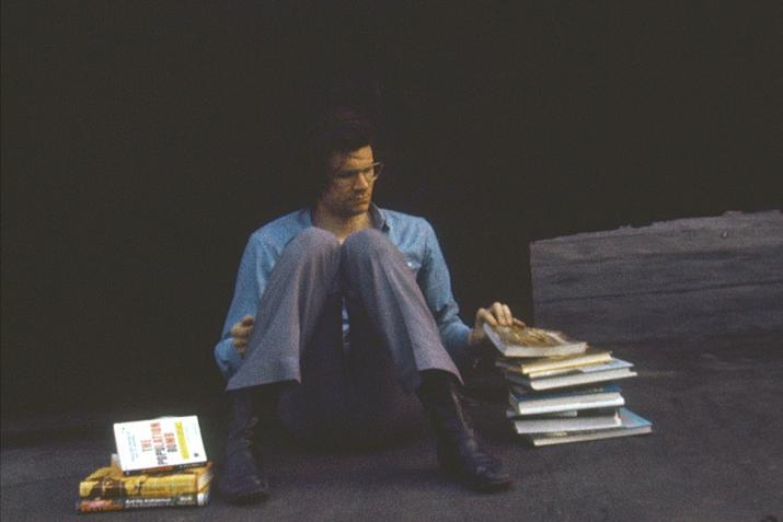 person sitting on the ground on a rooftop with a large pile of books beside them