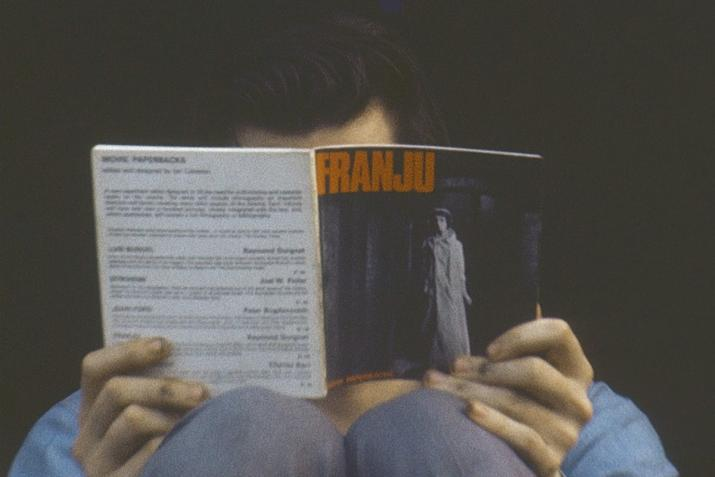 "person reading a book titled ""franjo"" while resting the book on their knees."