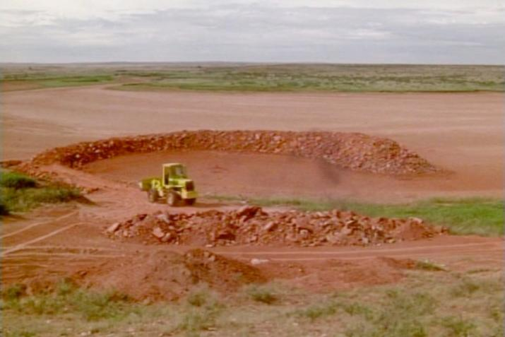 a bulldozer driving on a circular ramp of red earth