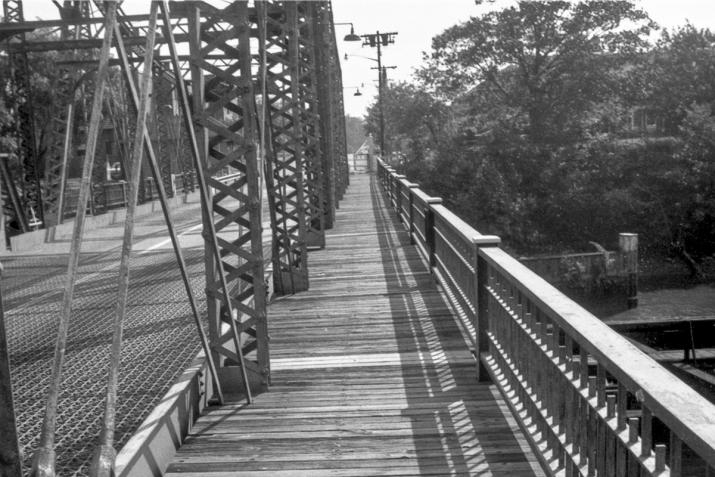 looking down a bridge with a wooden walkway in the center. black and white.