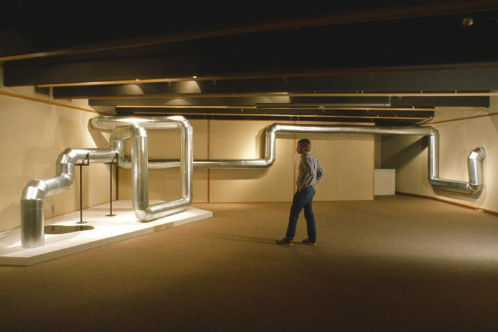 a person stands next to a sculpture made of metal pipe that zig zags through the air and along the wall in a basement room