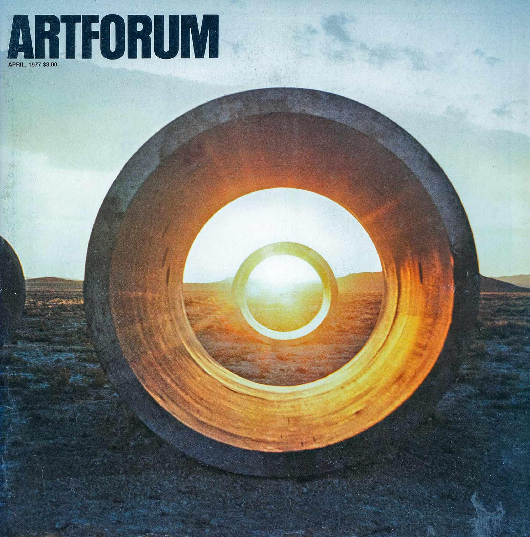 Magazine cover with the artforum logo in black in the upper left corner.  Cover image of two large concrete tunnels in line in the Utah desert, with the sun setting behind the second tunnel.
