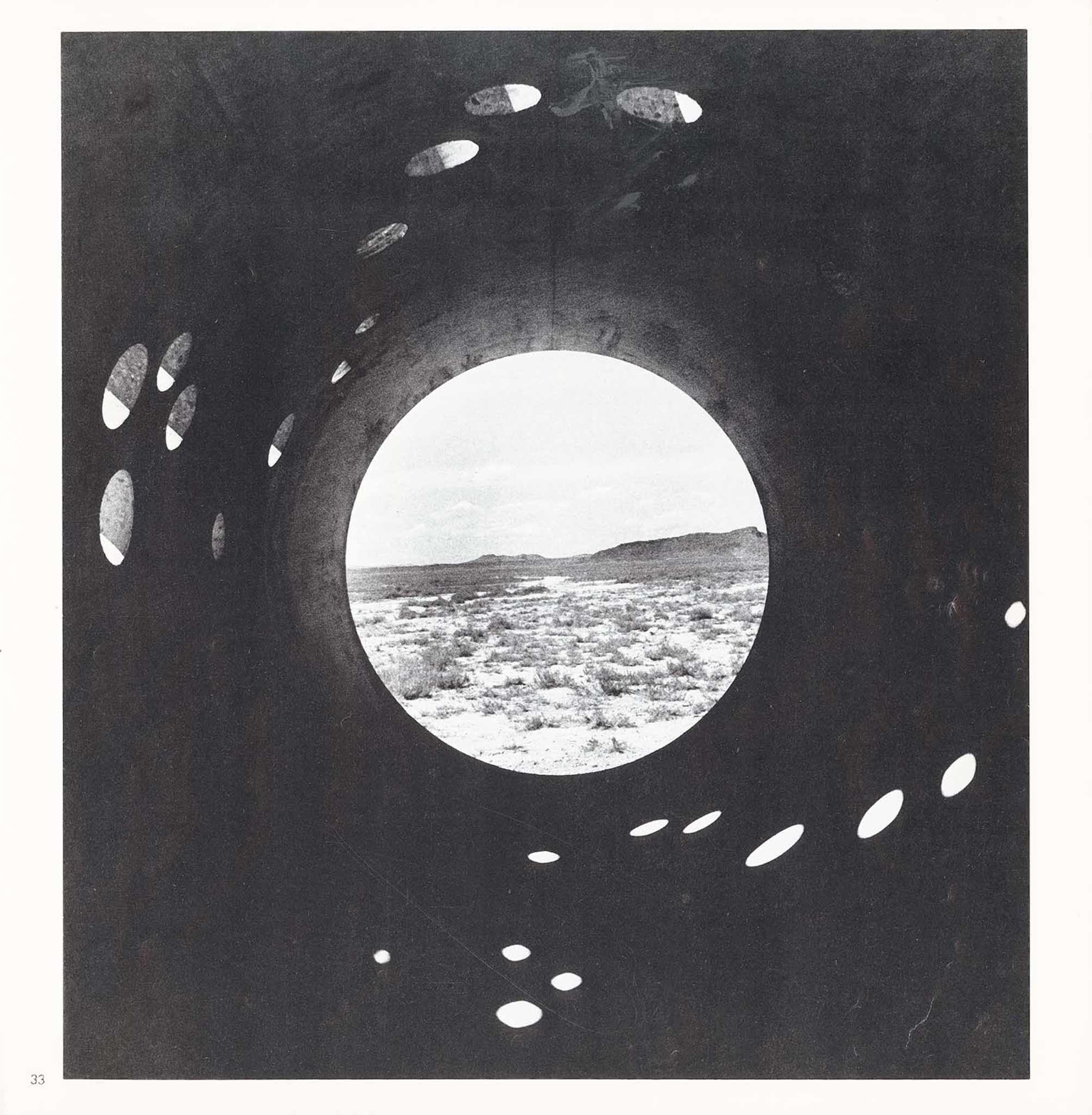 View inside a circular concrete tunnel looking out through a circular opening at the end onto the desert and mountains.  Small circular holes in the top and sides of the tunnel cast light onto the bottom of the tunnel.