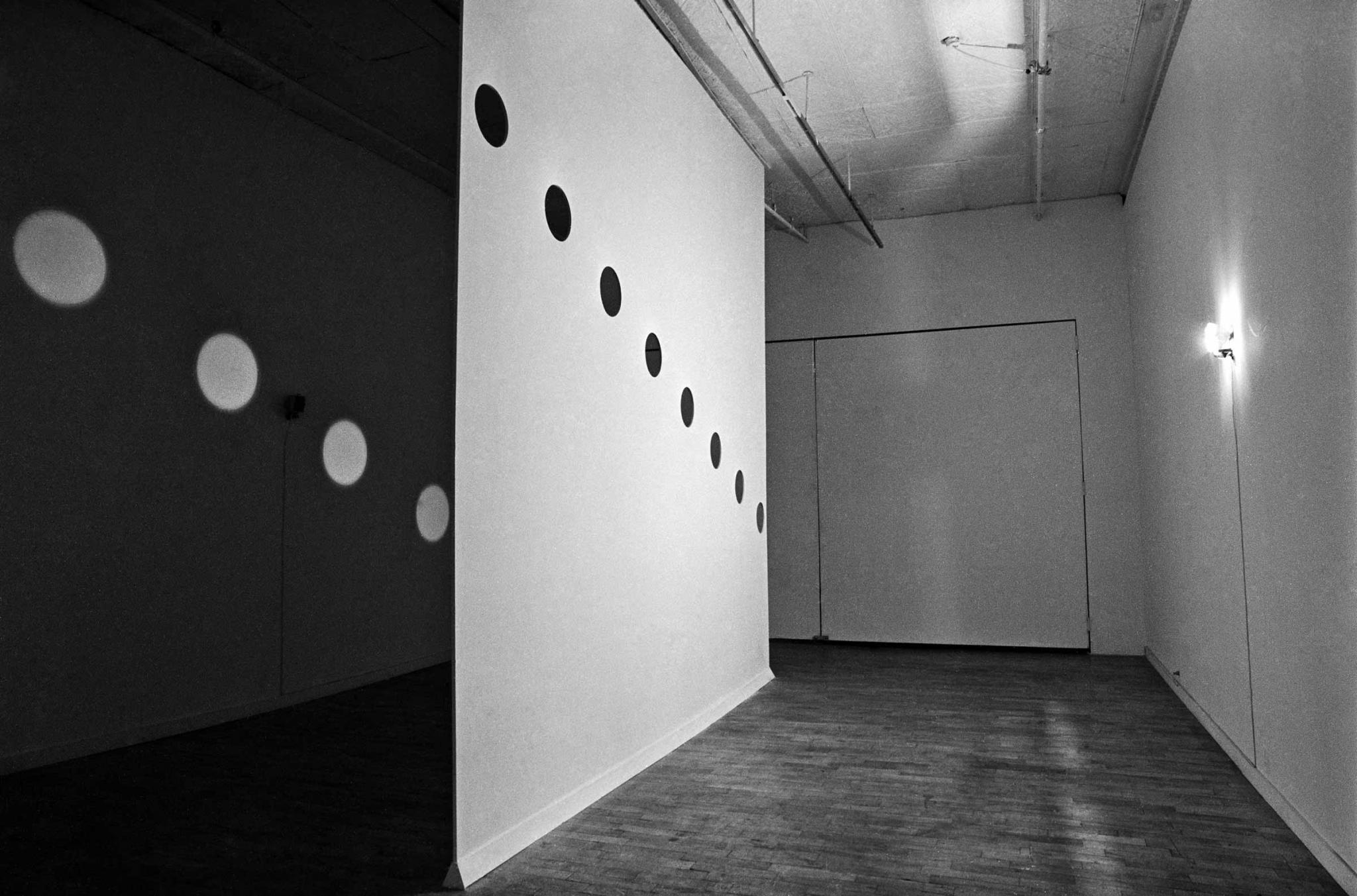 Room bisected by a wall with circular holes cut in it to let light pass through, creating orbs of light on the other side.