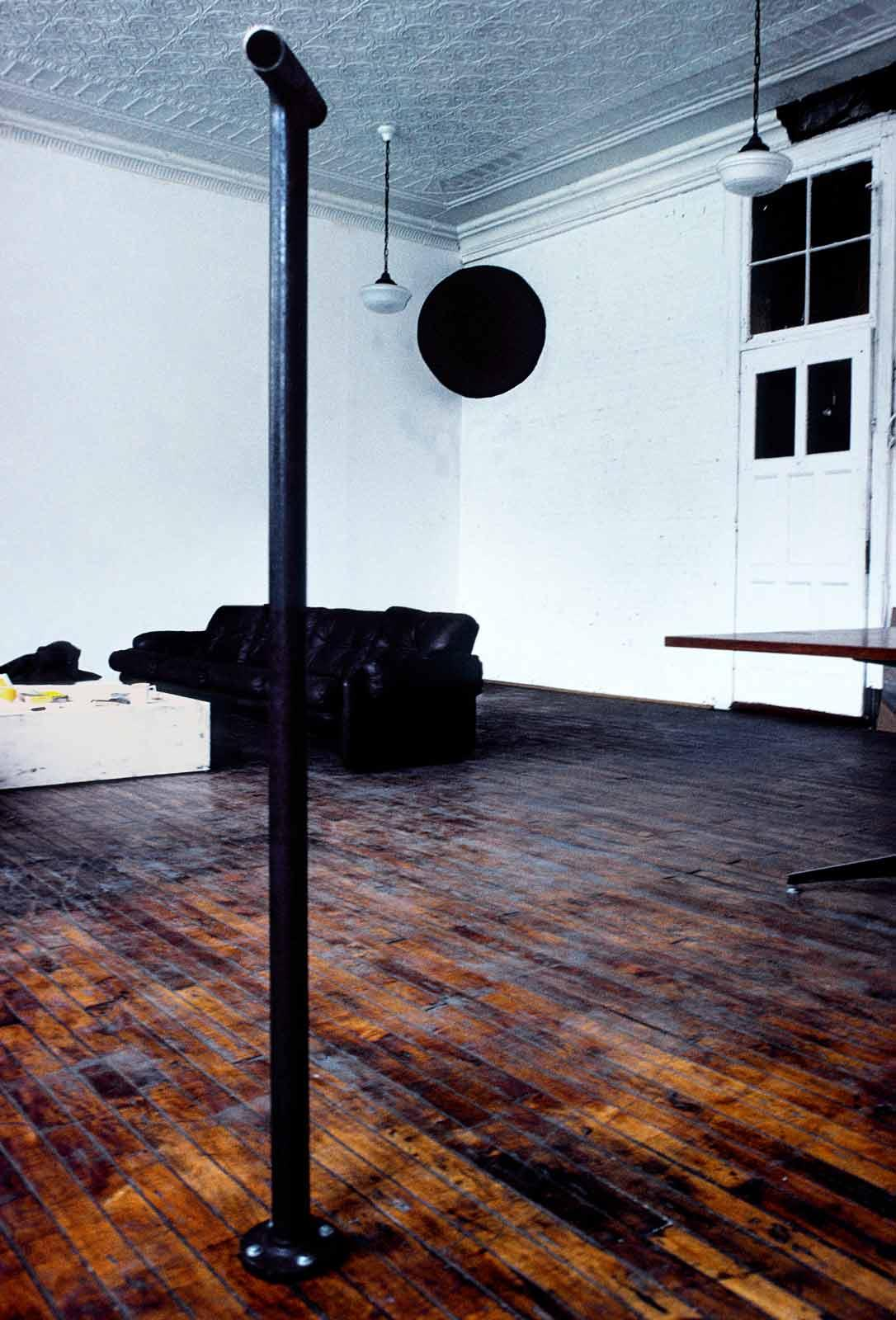 Stell pipe in a room with wood floors, white walls, and a black circle painted in the corner of the room.