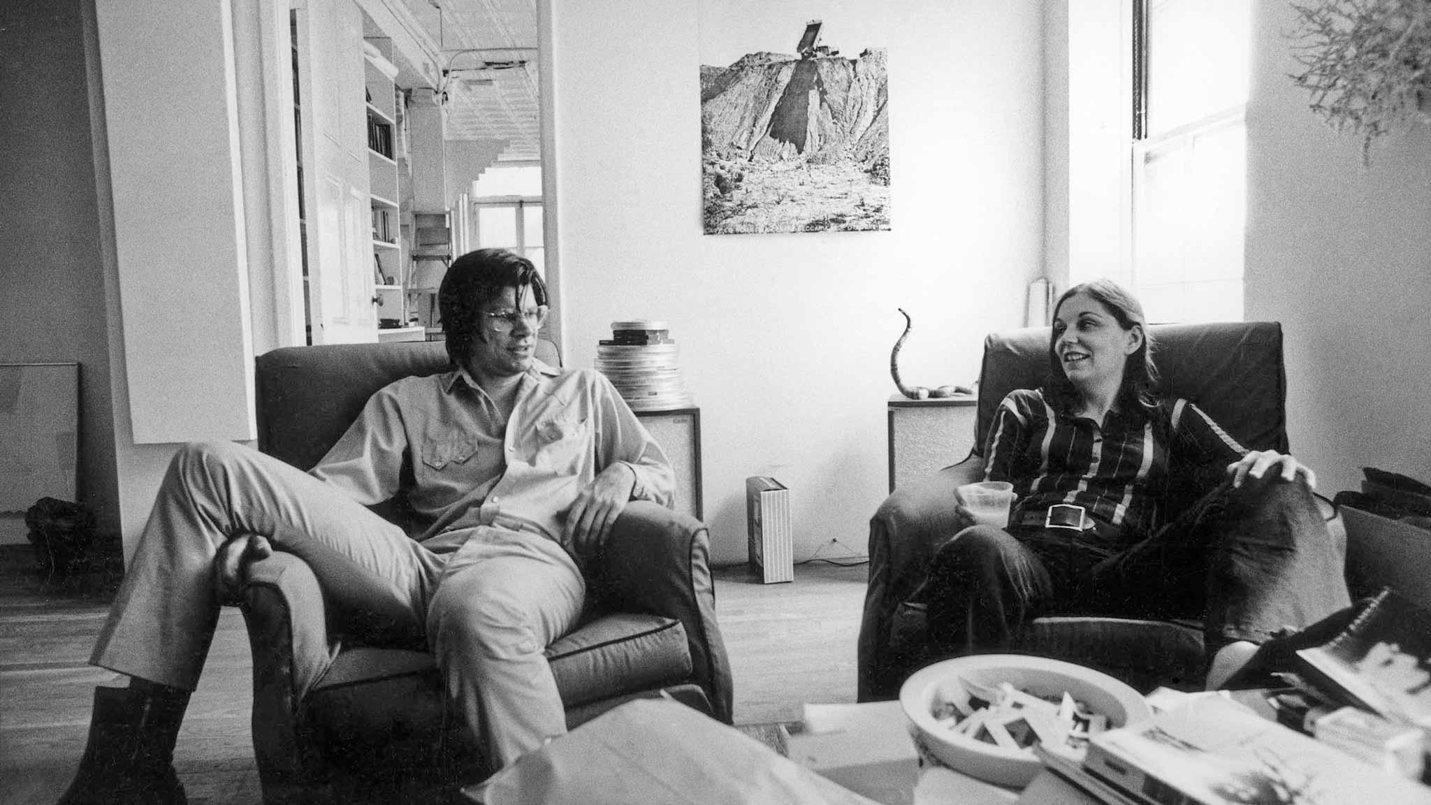 Black and white image of a man and woman seated next to each other in a living room