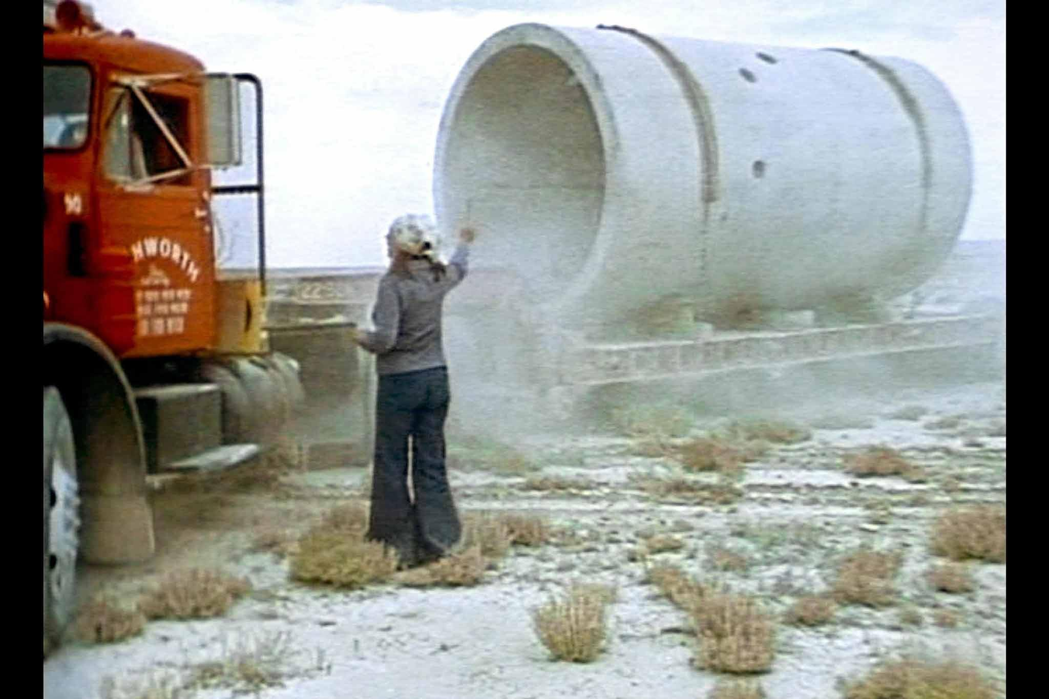 A film still from the construction of Holt's Sun Tunnels from the film, Sun Tunnels showing Holt directing a truck driver who is delivering one of the concrete tunnels.