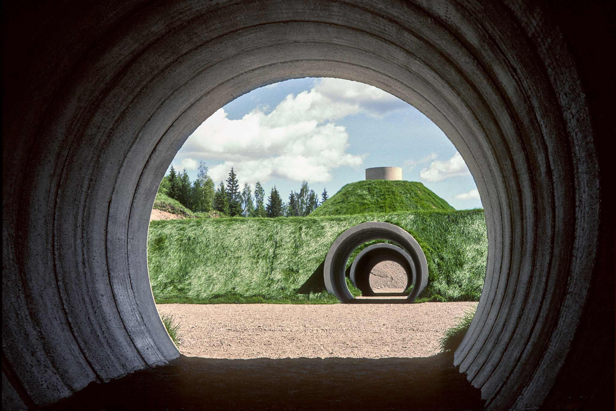 Interior view of a circular tunnel looking out onto a mound of earth with tunnels cutting through it.