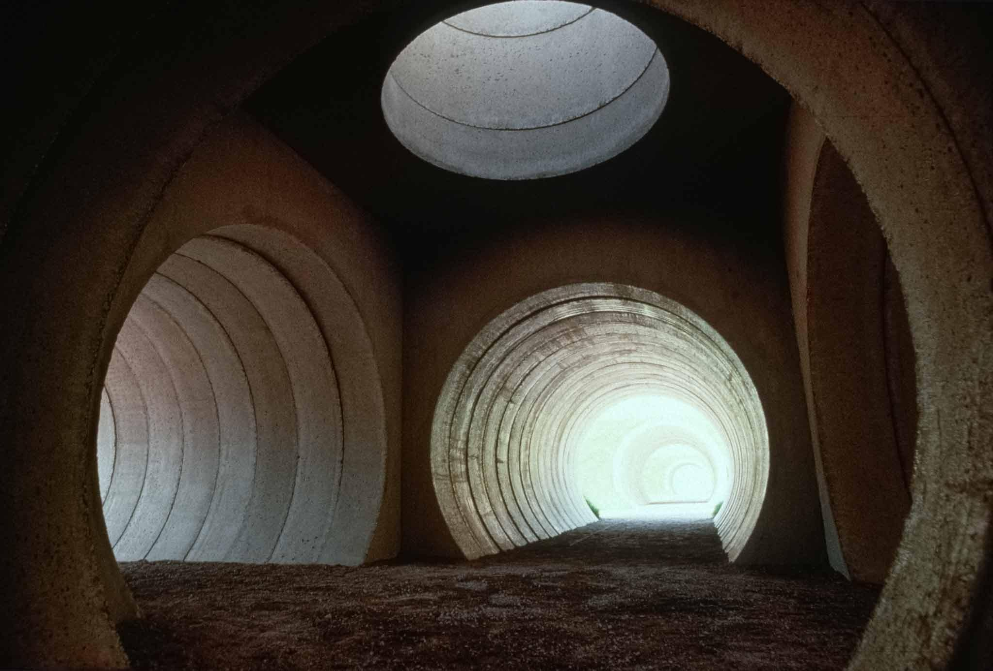 Interior view of converging circular concrete tunnels with light coming through them
