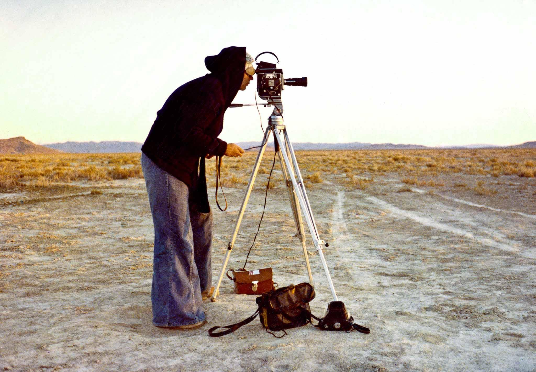 Nancy Holt filming the Spiral Jetty with her Bolex 16 millimeter film camera.