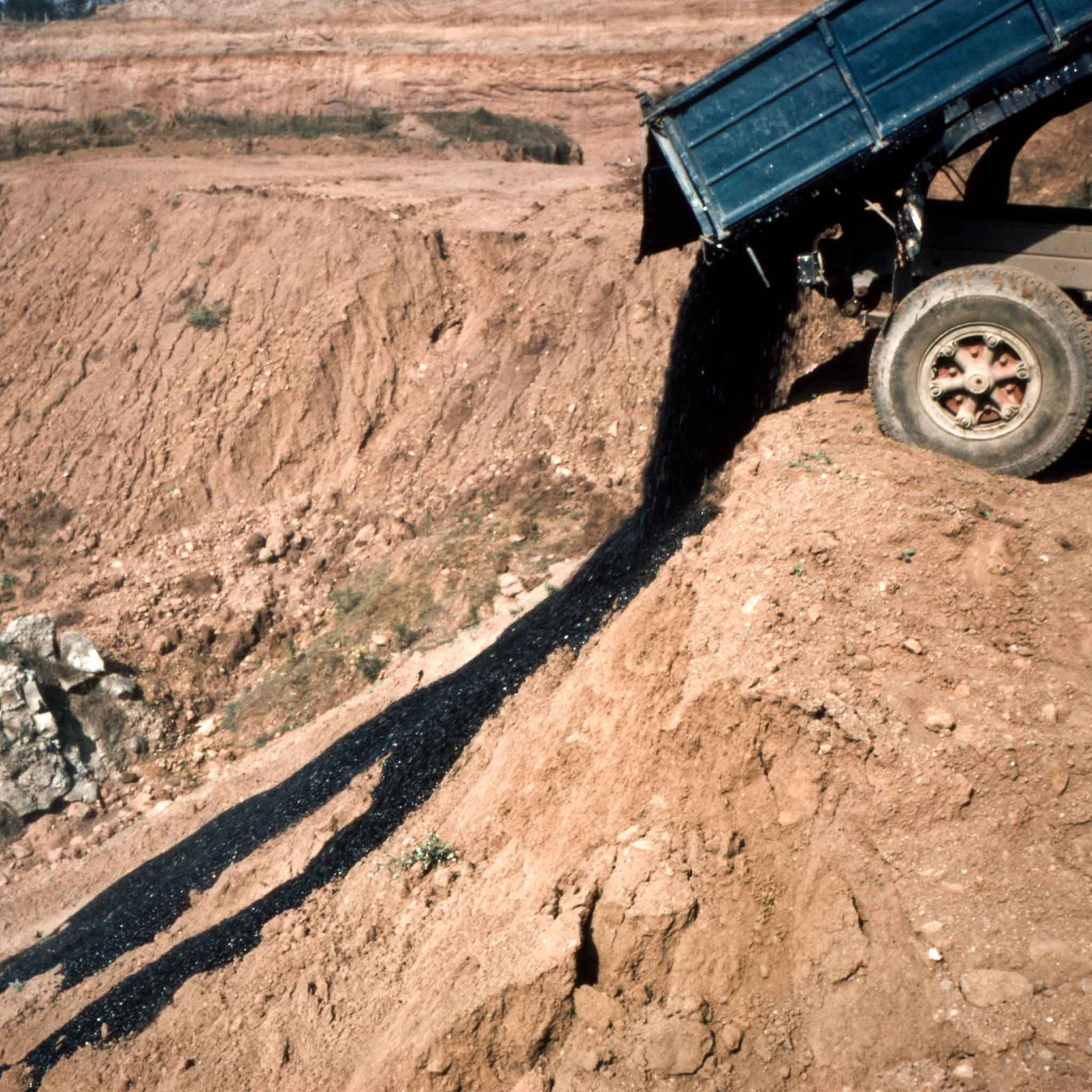 A dump truck unloads a large amount of asphalt which runs down the side of a hill outside of Rome, Italy.