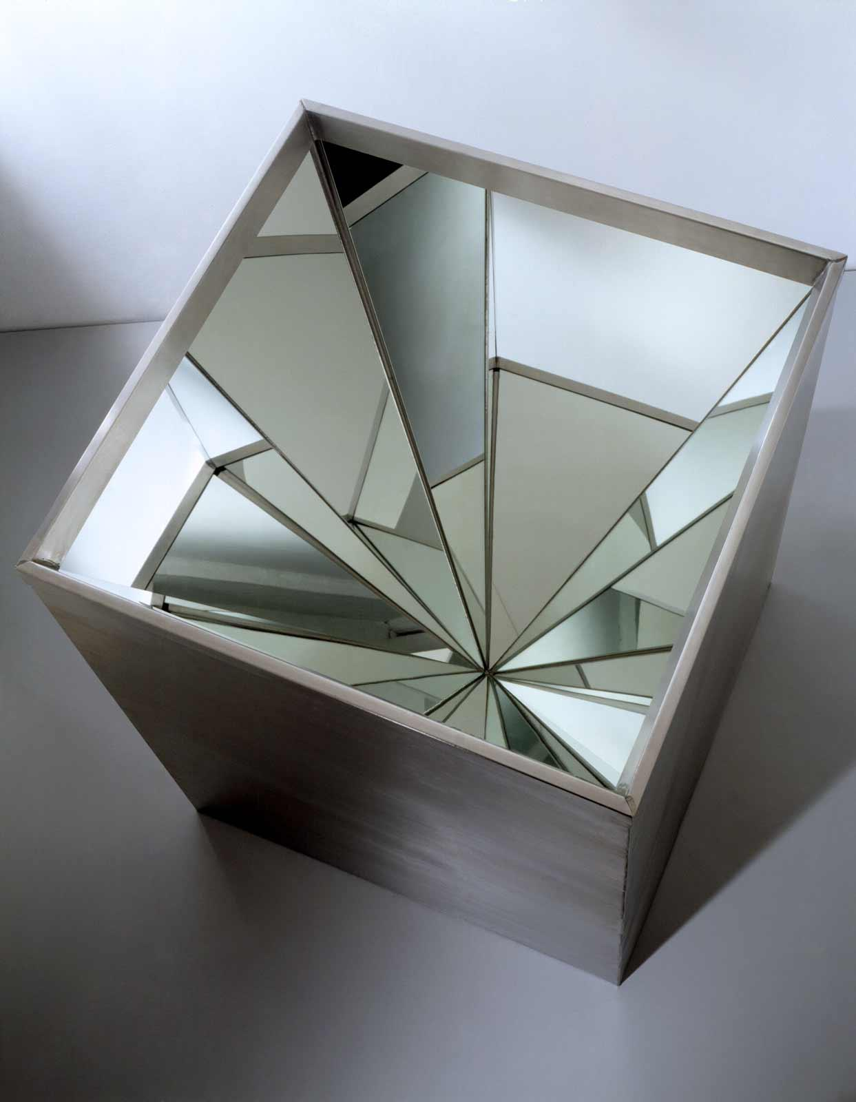 A 28 x 28 inch metal box that is open on the top and lined with four triangular mirrors at meet at their apex.