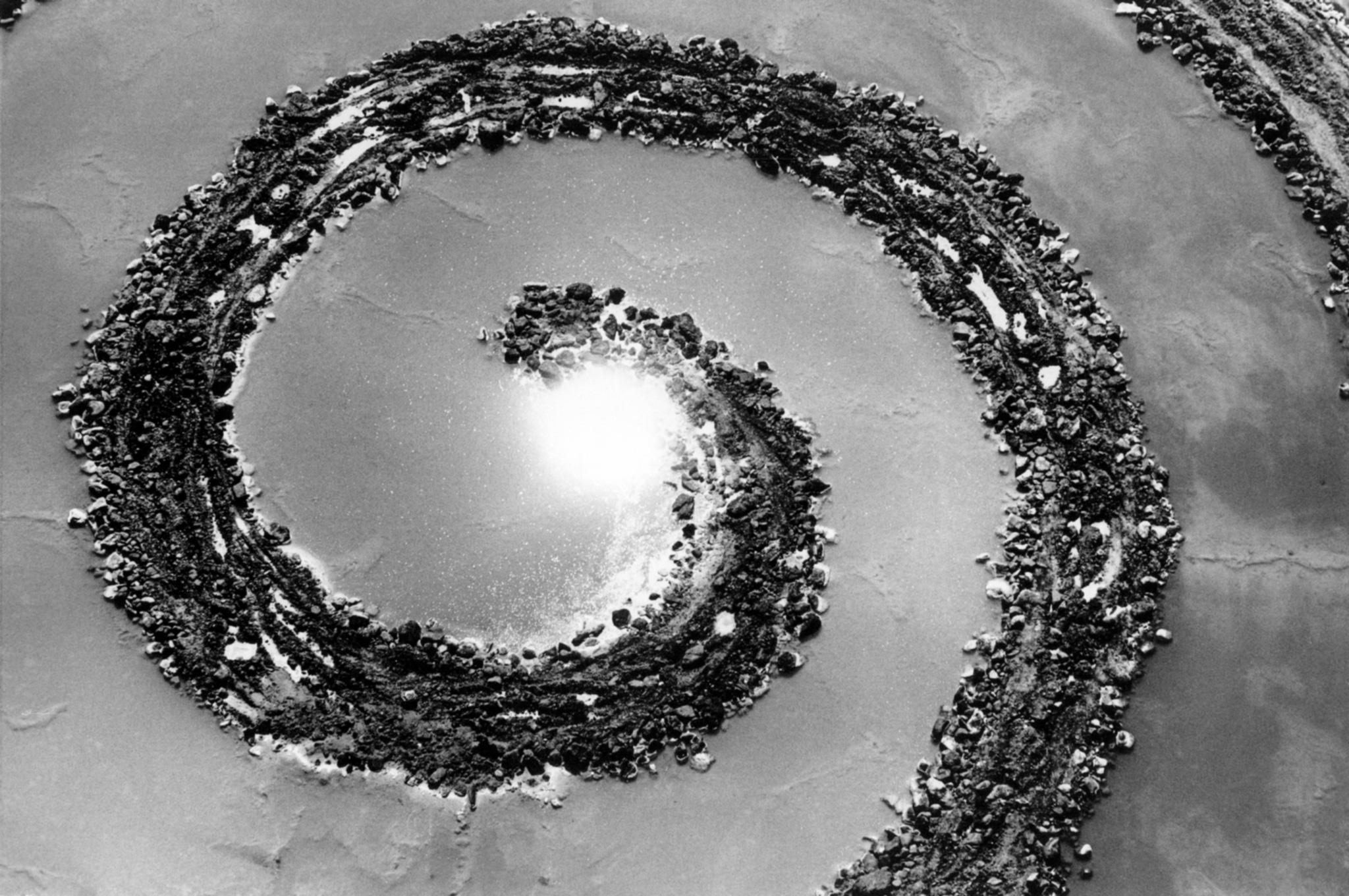 aerial black and white image of a spiral of rocks and earth in water. Sun reflected in water.
