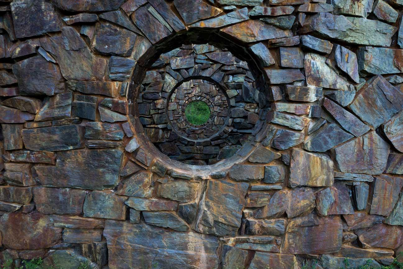 Stone walls receding in space with concentric circular holes in the center.