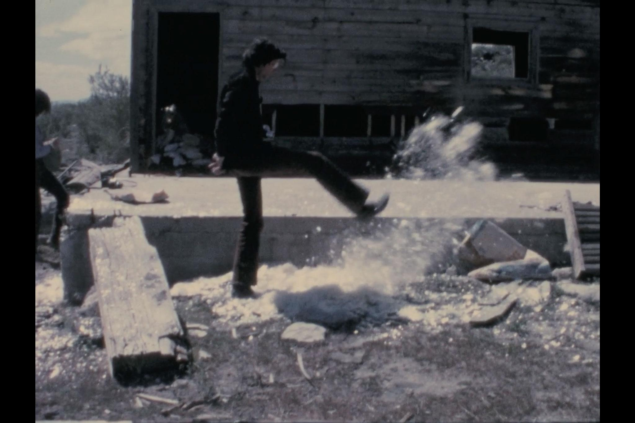 a man kicks a pile of mica and the mica spreads out and flies through the air