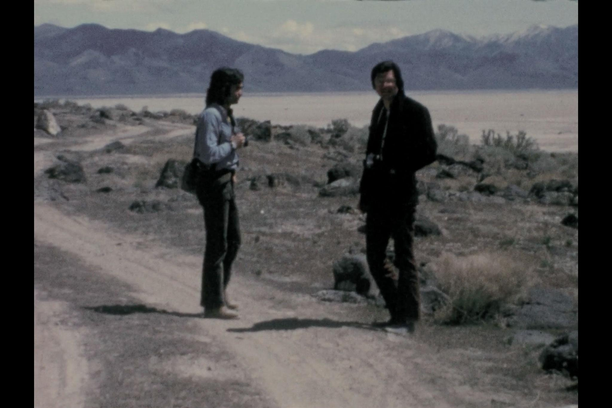 Two figures standing on a dirt road with mountains in the background