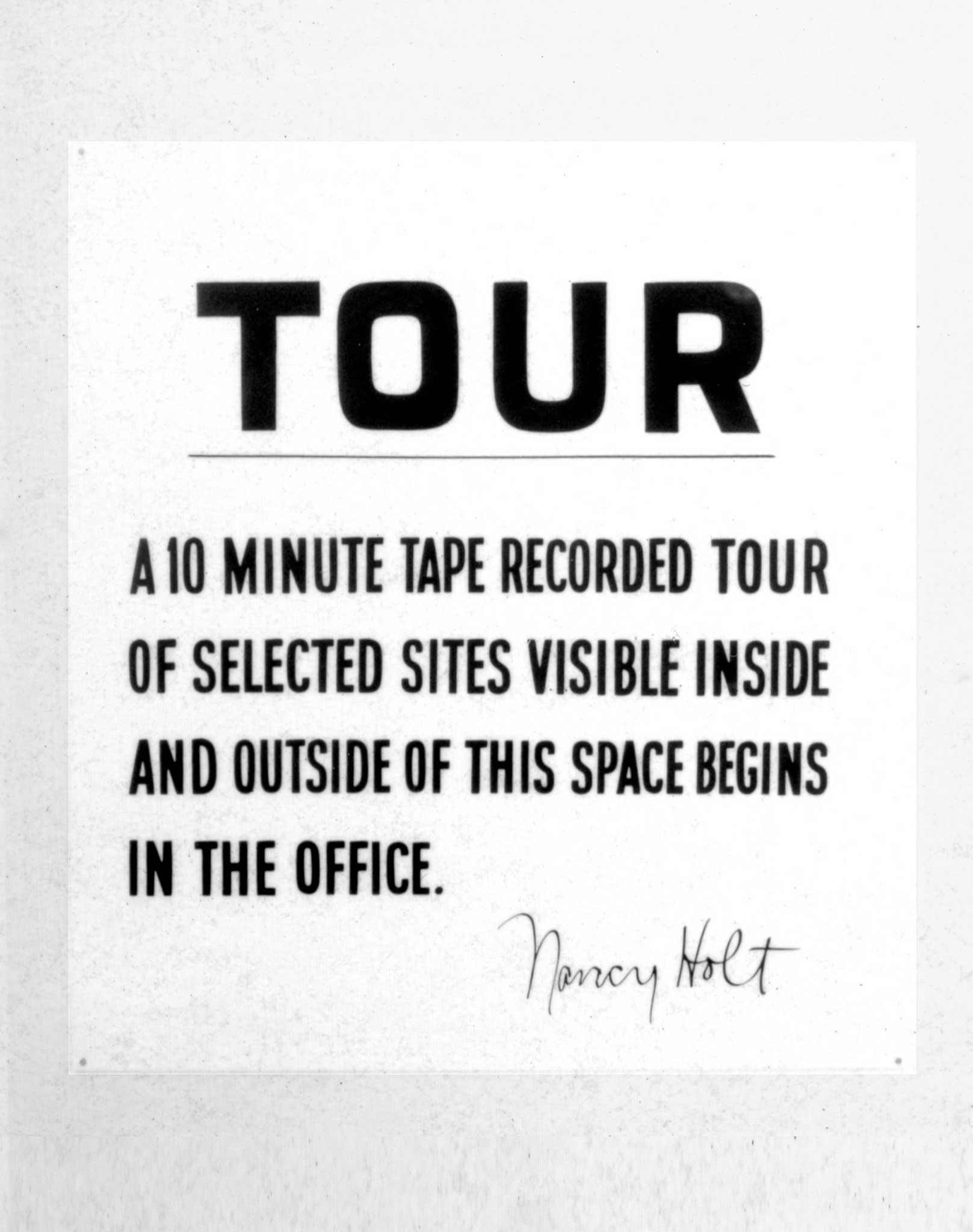 "A sign that reads ""Tour. a 10 minute tape recorded tour of selected sites visible inside and outside of this space begins in the office"""