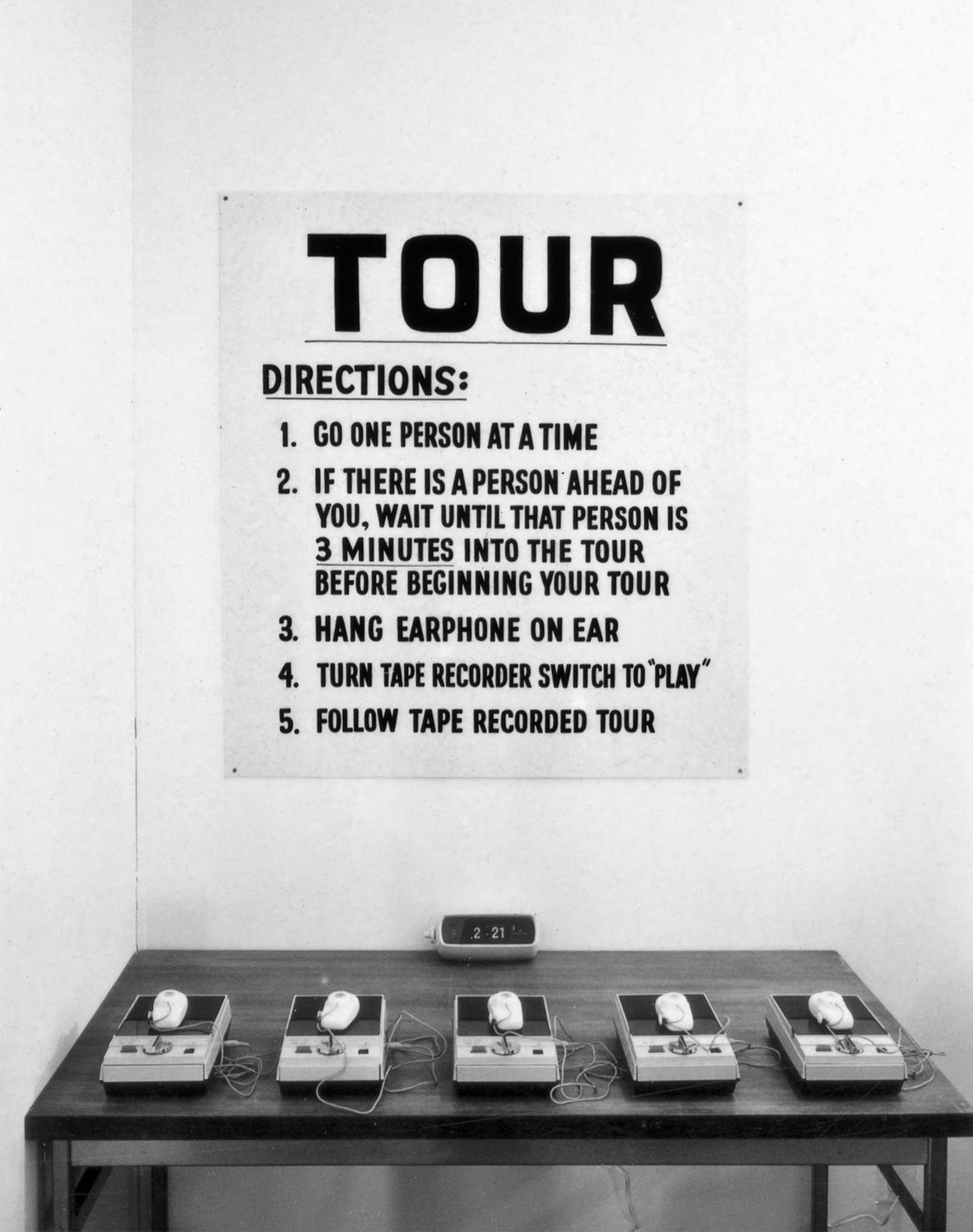 A table with five portable tape recorders and a large sign above it with directions for a guided audio tour