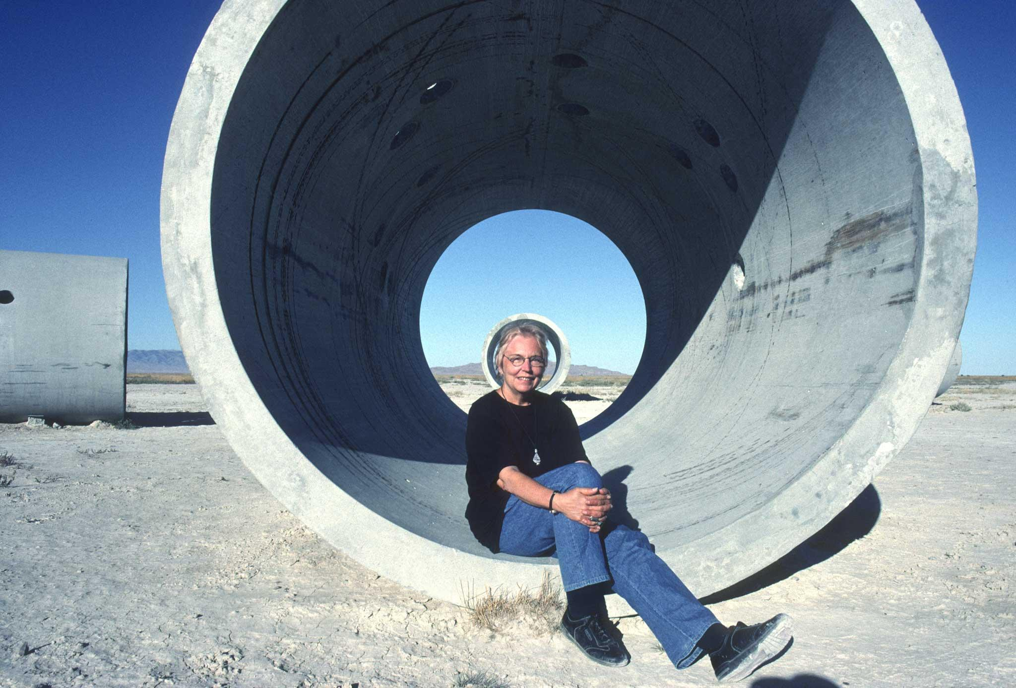 woman seated at the center of a large circular concrete tunnel with blue skies in the background.
