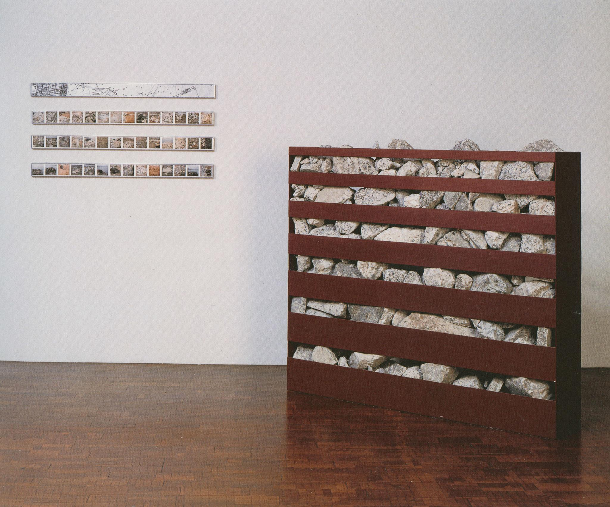 A metal bin positioned on the floor with horizontal openings that contains broken concrete. Four framed horizontal images on the wall behind the bin.