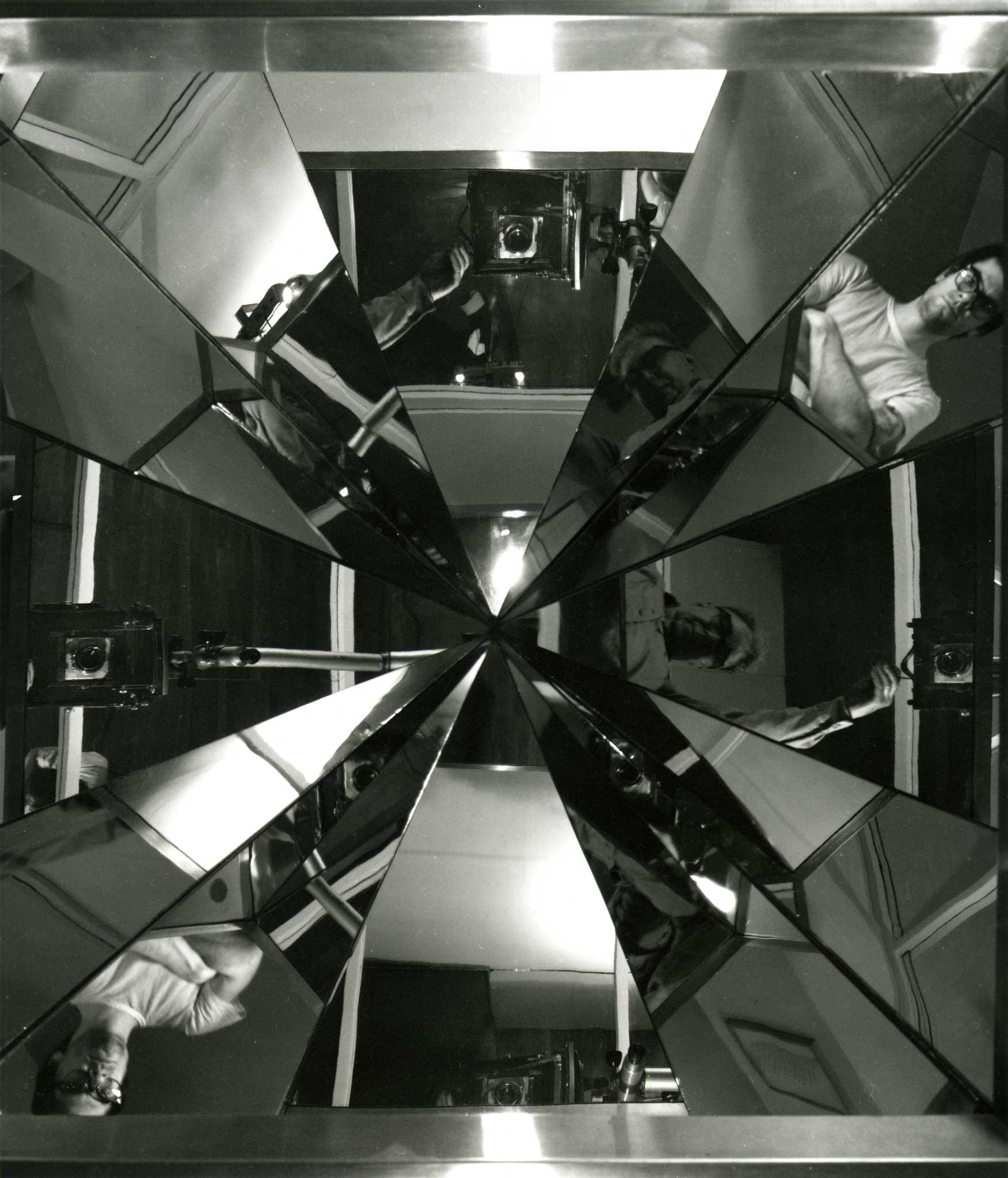 black and white image of angular reflections converging at a center point.  Reflections are of of two men standing looking into the mirrors