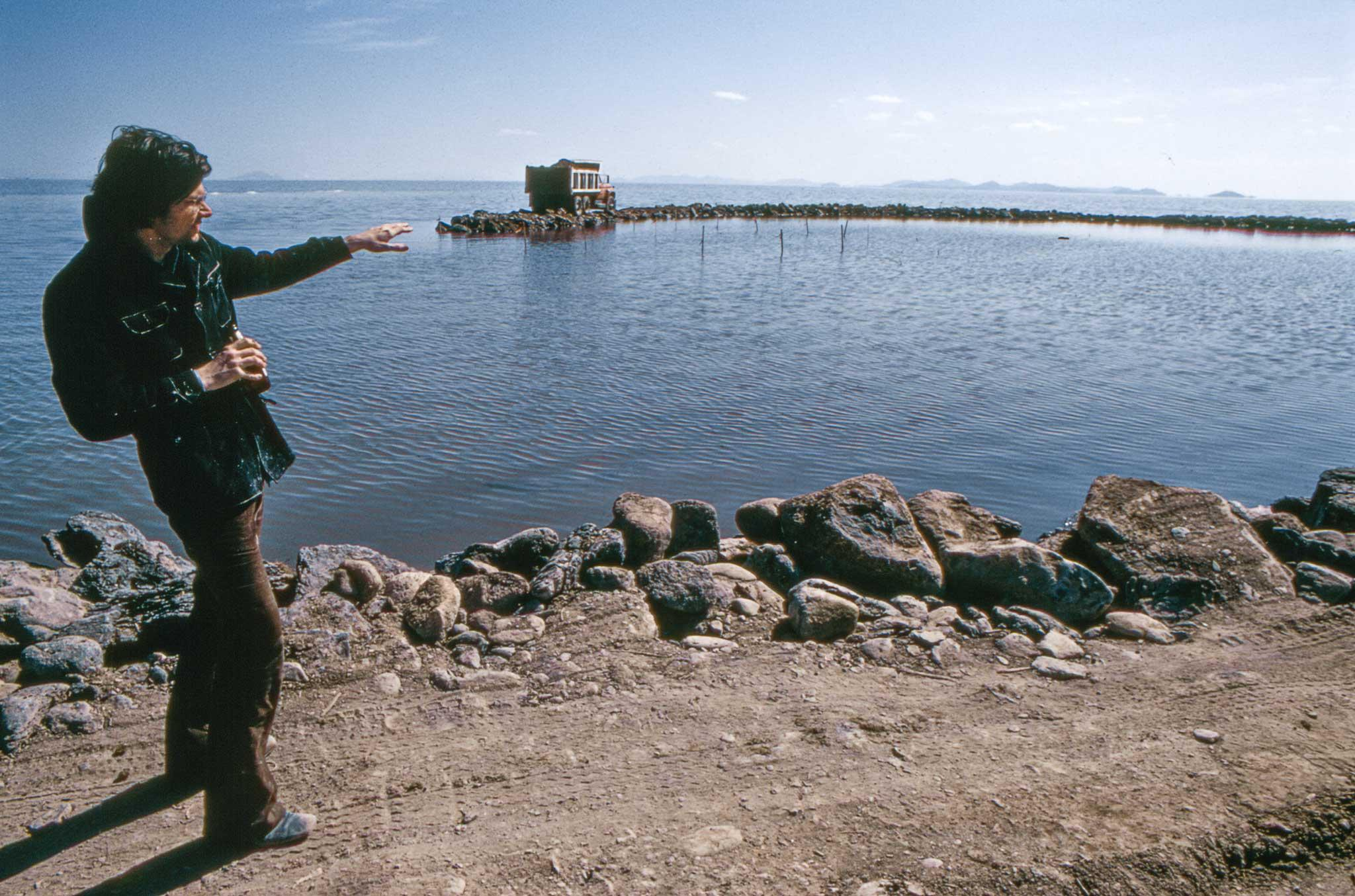 Man standing on the left side of the frame gesturing toward a jetty of land and a truck on the water